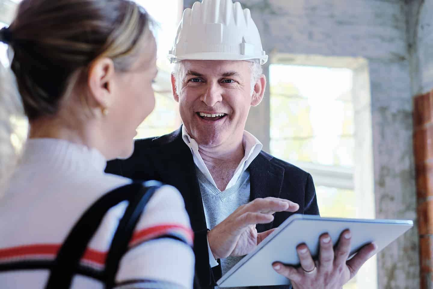 Sales agent talking with client in new building. Man working as realtor in construction site with customer. Real estate broker showing home to woman.